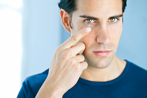 Vision: man using a contact lens stock photo