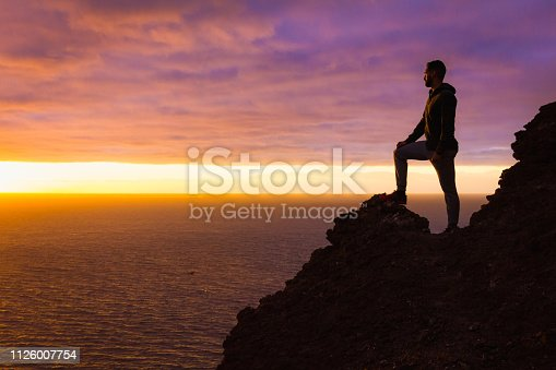 Silhouette of person witnessing unique twilight from mountain top. Successful, entrepreneur concepts