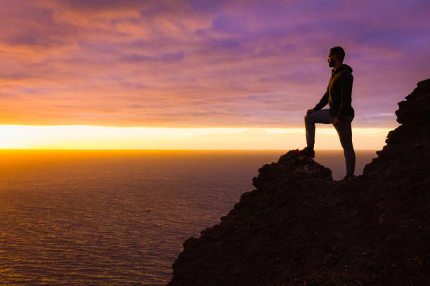Visionary man standing on top of cliff edge staring at colorful sunset by the sea in Gran Canaria stock photo