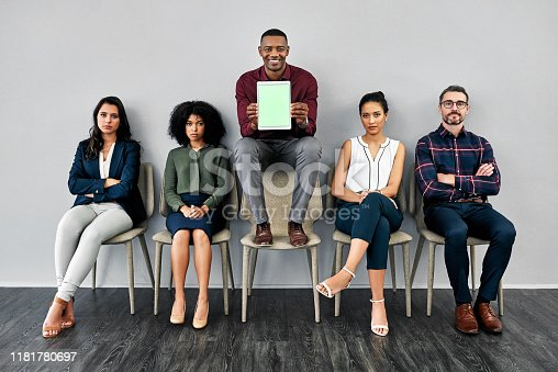 Studio shot of a young businessman surrounded by job candidates holding a digital tablet with a green screen