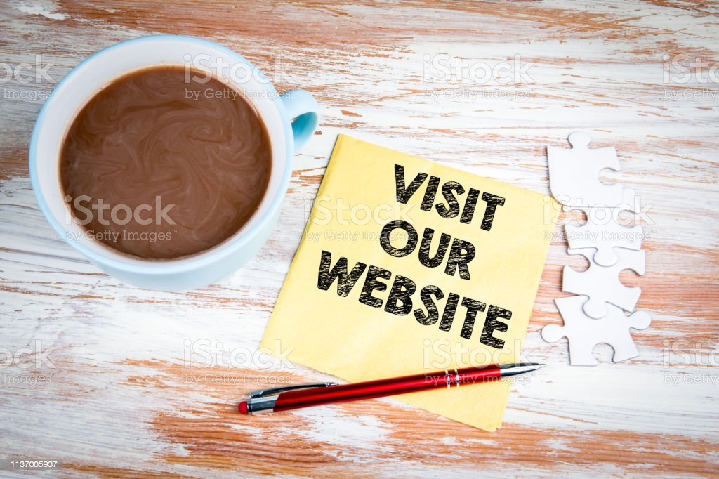 Visit Our Website. Text on a napkin with a cup of coffee