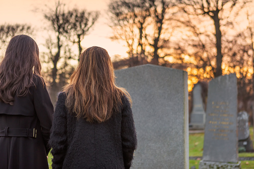 Two mourning persons standing in front of a grave at the graveyard.