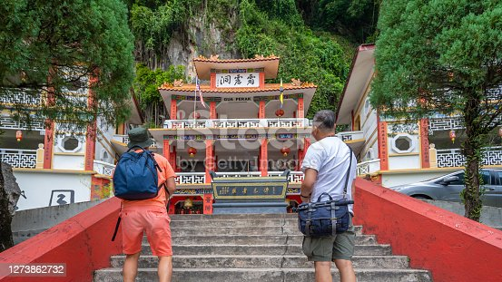 Rear shot of two Asian men about to visit a Chinese temple.