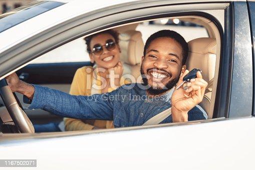 istock Visiting car dealership. Afro couple showing car key 1167502071