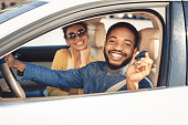 Visiting car dealership. Afro couple showing car key, looking at camera and smiling, sitting in new car