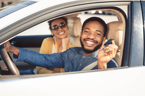 in visita alla concessionaria di auto. coppia afro che mostra la chiave dell'auto - auto foto e immagini stock