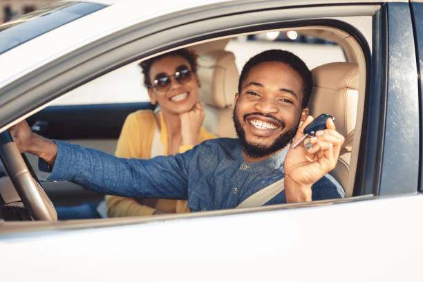 Visiting car dealership. Afro couple showing car key Visiting car dealership. Afro couple showing car key, looking at camera and smiling, sitting in new car car stock pictures, royalty-free photos & images