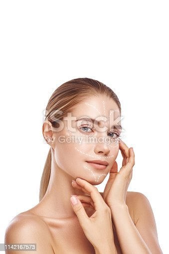 istock Visiting cosmetic clinic. Vertical photo of gorgeous woman touching her clean and healthy face with with lifting arrows on it. Isolated on white background. Face lifting concept 1142167573