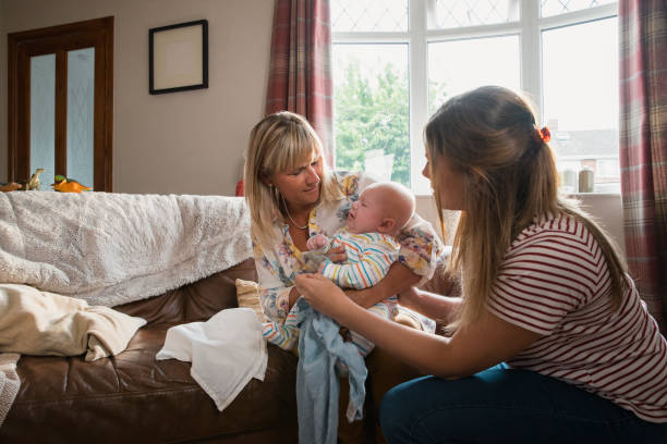 Visiting Her Newborn Grandson Mid adult mother is at home with her baby son. His grandmother is visiting and helping to look after the baby as he is crying. visit stock pictures, royalty-free photos & images