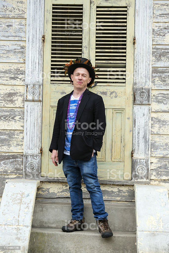 Mardi Gras man standing on steps in French Quarter royalty-free stock photo