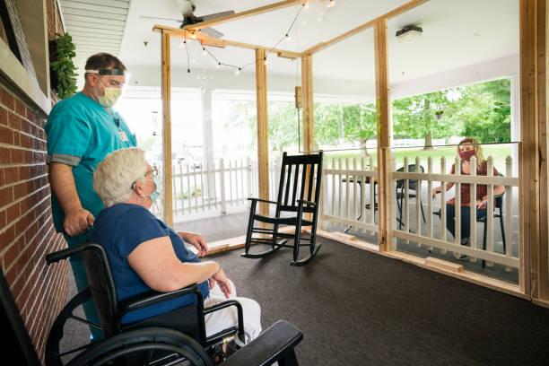 het bezoeken van patiënten van aangezicht tot aangezicht veilig in een verpleeghuis - raam bezoek stockfoto's en -beelden