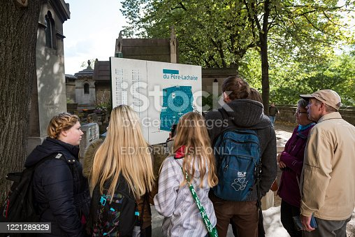 Tourists visiting Père Lachaise Cemetery in Paris consult a map near the entranace to the cemetery. The cemetery is a popular tourist destination in Paris, France