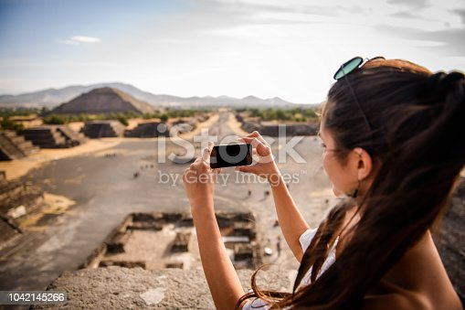 Smiling woman taking a photo of the Teotihuacan,Mexico