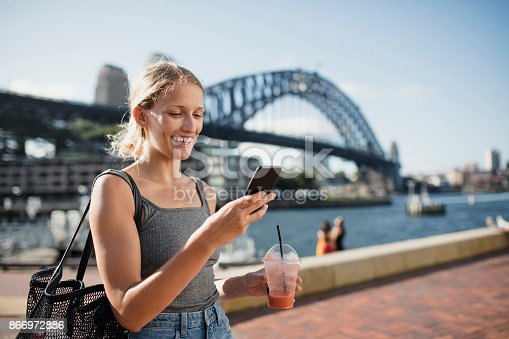 A woman uses her phone with a view of Sydney Harbour Bridge in the background.