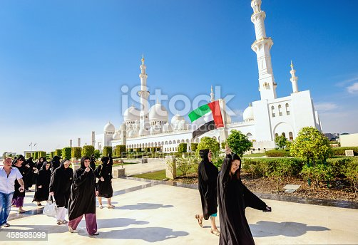 Abu Dhabi, United Arab Emirates - November 10, 2012: Tourist guide leading a group of tourists at the majestic Sheikh Zayed Mosque in Abu Dhabi (UAE). Female visitors are asked to wear a traditional robe (Abaya) and headscarf.