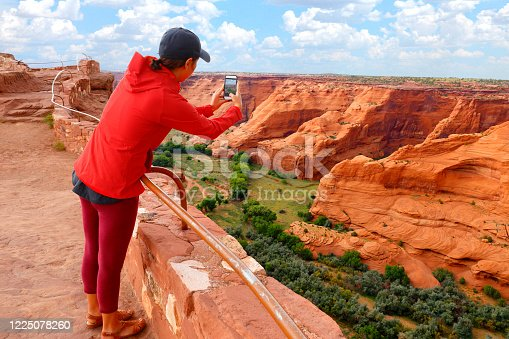A young female visitor reaches over a hand rail and takes a picture with her smart phone at the Canyon de Chelly National Monument in eastern Arizona.
