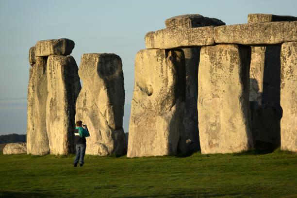 Visitor explores photographs sunrise Stonehenge Salisbury Plain Wiltshire England stock photo