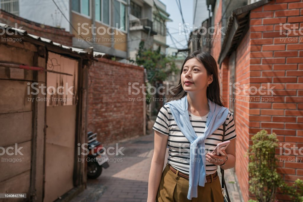visitor strolling in the alley by holing a phone. stock photo