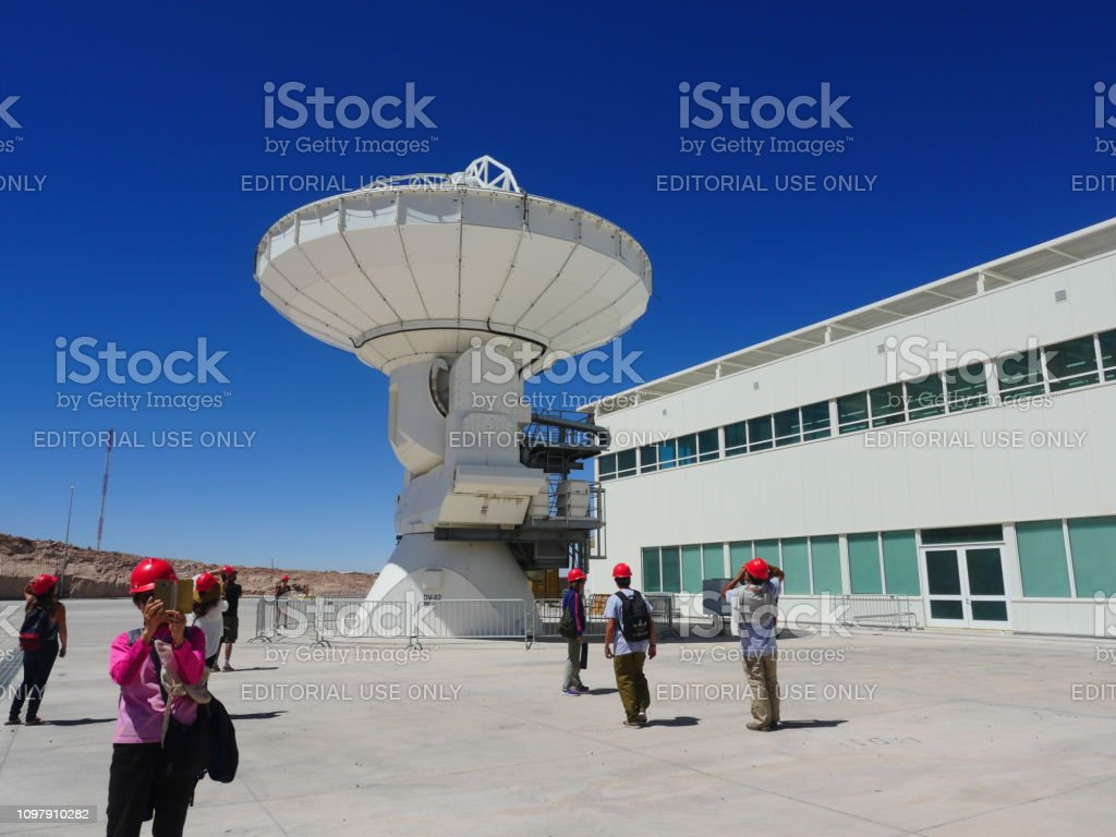 Visitors at Alma Observatory next to a large antenna in San Pedro de Atacama, Chile stock photo