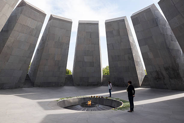 Visitors at Armenian Genocide Memorial in Yerevan Yerevan, Armenia - October 4, 2016: Two visitors stand next to the eternal flame at the Armenian Genocide Memorial in Yerevan, Armenia.  The twelve slabs in a circle surrounding the flame represent the twelve lost provinces in present-day Turkey. armenian genocide stock pictures, royalty-free photos & images