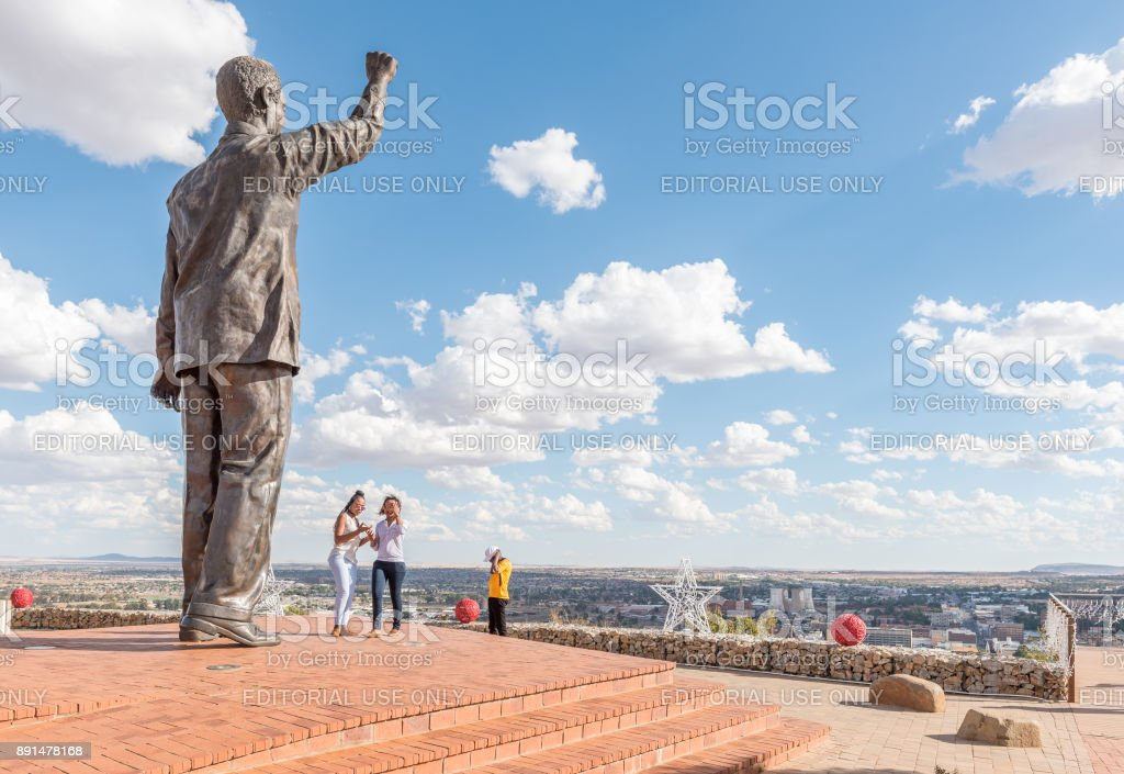 Visitors at the bronze statue of Nelson Mandela in Bloemfontein stock photo