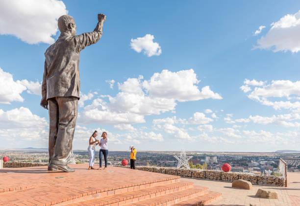 Visitors at the bronze statue of Nelson Mandela in Bloemfontein stock photo