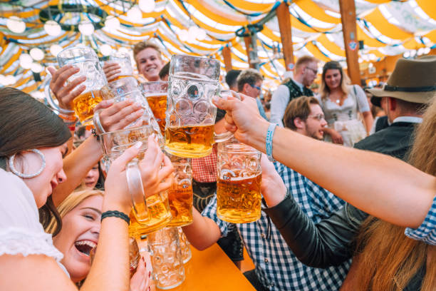 Besucher feiern Oktoberfest im Bierzelt, München, Deutschland – Foto
