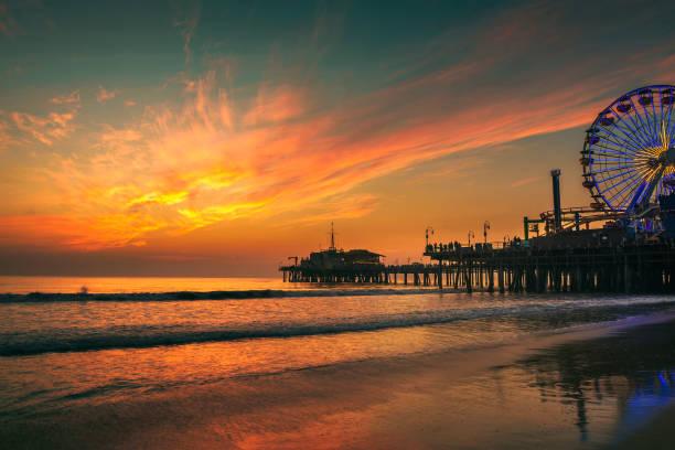 besucher genießen sie den sonnenuntergang über dem santa monica pier in los angeles - venice beach in kalifornien stock-fotos und bilder