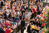 Munich, Germany - September 21, 2019: visitors sitting outdoors at tables, eating and drinking beer at Oktoberfest in Munich