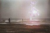 Man looking at mysterious aliens materializing on the beach