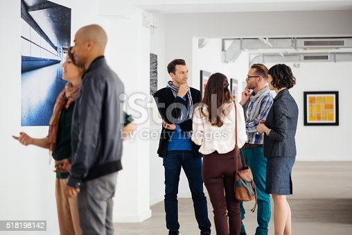 People in an art gallery looking at artwork. It's a gallery opening with artist and gallery owner guiding people through the exhibition. In the picture the gallery owner explaining art to an interested group of visitors.