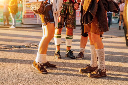 Visitors in lederhosen walking through beer festival fairgrounds