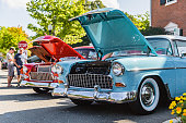 Matthews, North Carolina -  September 3, 2018: Visitors admire vintage 1950s era Chevrolet and Ford cars parked on display at the Matthews Auto Reunion