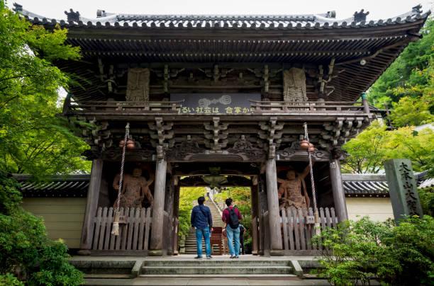 宮島の大正院寺の木造ビルで、ニオ王像を持って門の入り口を見る来場者 - 鬼門 ストックフォトと画像