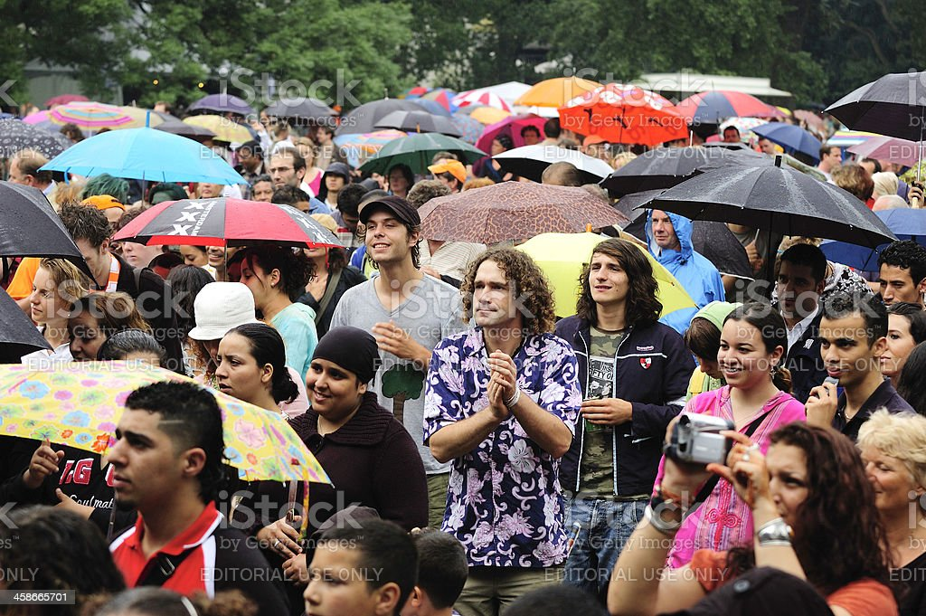 Visitors of a music festival standing in the rain stock photo