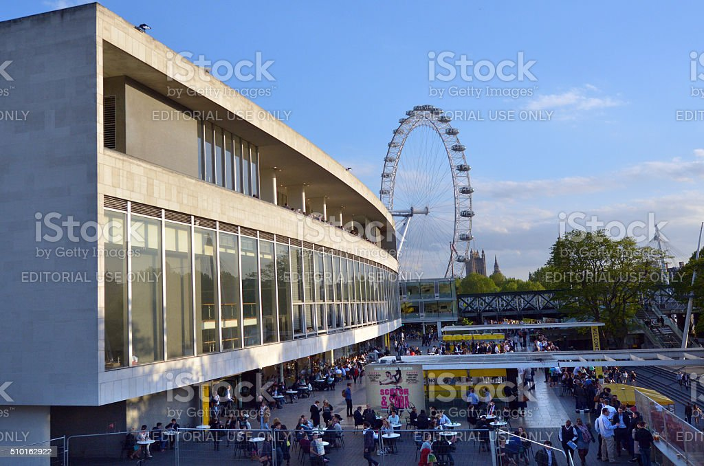 Visitors outside the Royal Festival Hall in with London Eye stock photo