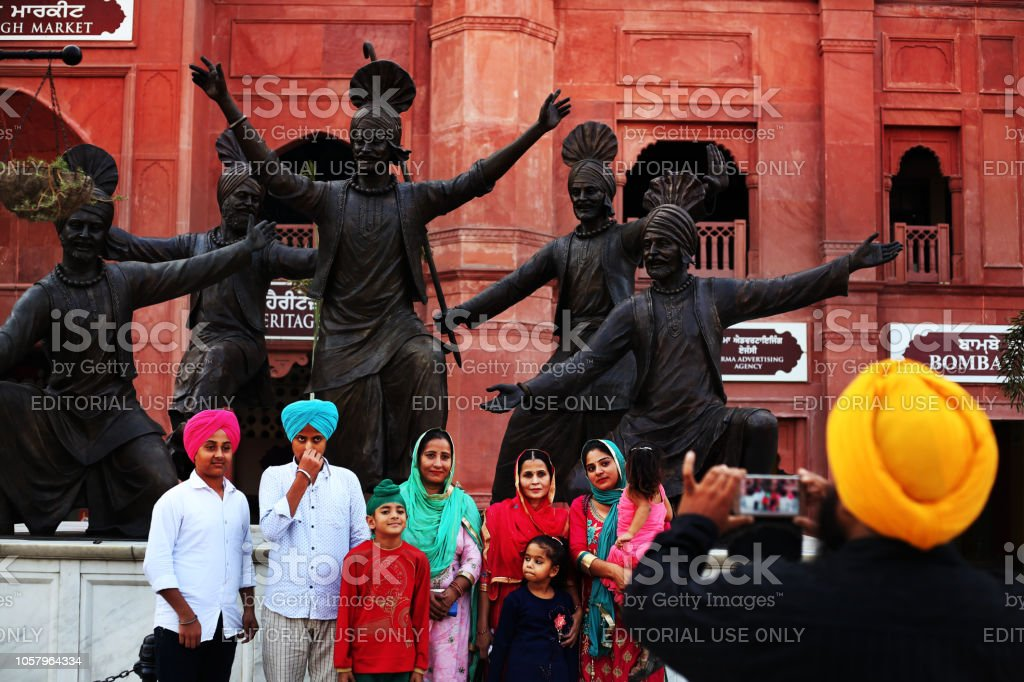 Visitors pose in front of statues of bhangra dancers near Dharam Singh Market, Amritsar Punjab, India stock photo