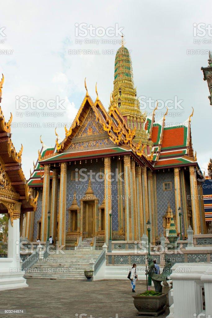 Bezoekers rust in de schaduw van de Prasat Phra Thep Bidon op de Wat Phra Kaeo foto