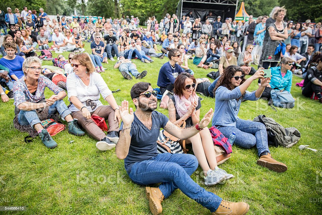visitors sitting on the grass, Amsterdam Roots Open Air festival stock photo
