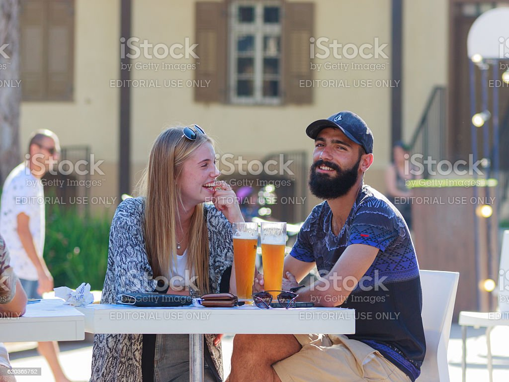 Visitors to annual festival of beer sitting at table zbiór zdjęć royalty-free