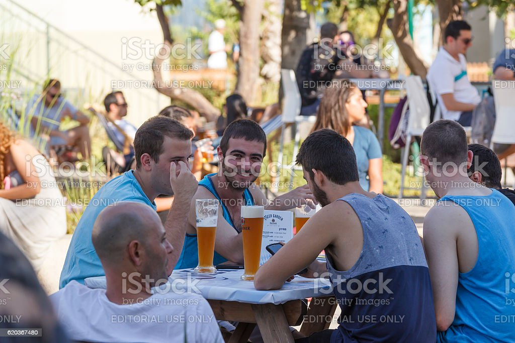 Visitors to annual festival of beer sitting at table foto de stock royalty-free