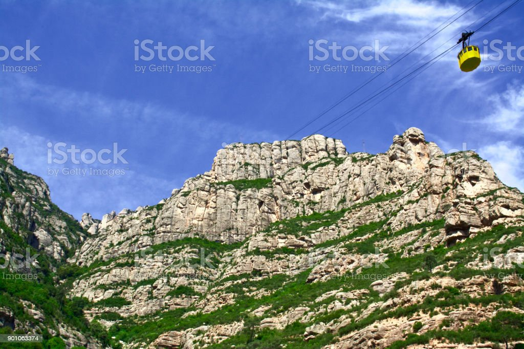 Visitors to the Abbey of Montserrat Ride the Yellow Gondolas to a beautiful Blue Sky stock photo