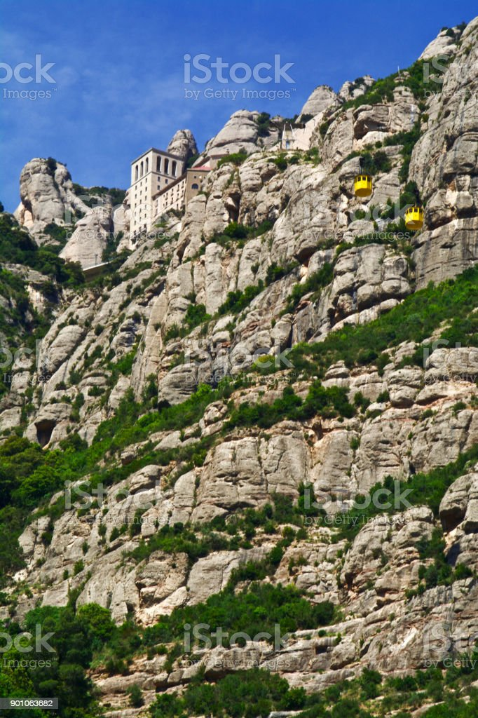Visitors to the Abbey of Montserrat Ride the Yellow Gondolas to a Heavenly Blue Sky stock photo