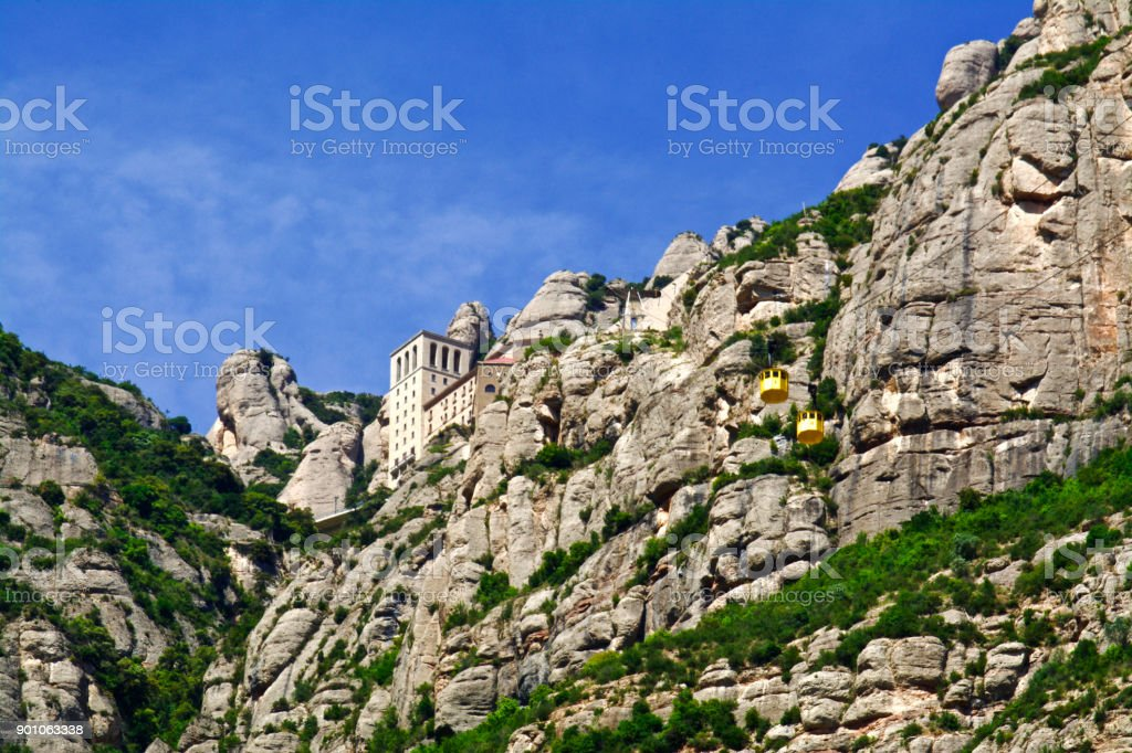 Visitors to the Abbey of Montserrat Take the Yellow Gondolas to a Heavenly Blue Sky stock photo