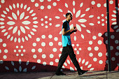 A young man walks past a colorfully patterned wall on a visit to the Wynwood Arts District during Art Basel Miami Beach 2017