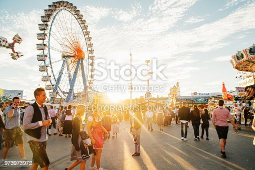 Munich, Germany - September 29, 2016: Visitors Walking Through Oktoberfest Fairgrounds at sunset, Ferris Wheel in the background.