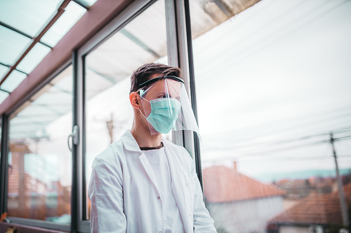Young doctor with a protective equipment agaist corona virus, wearing a mask and visor