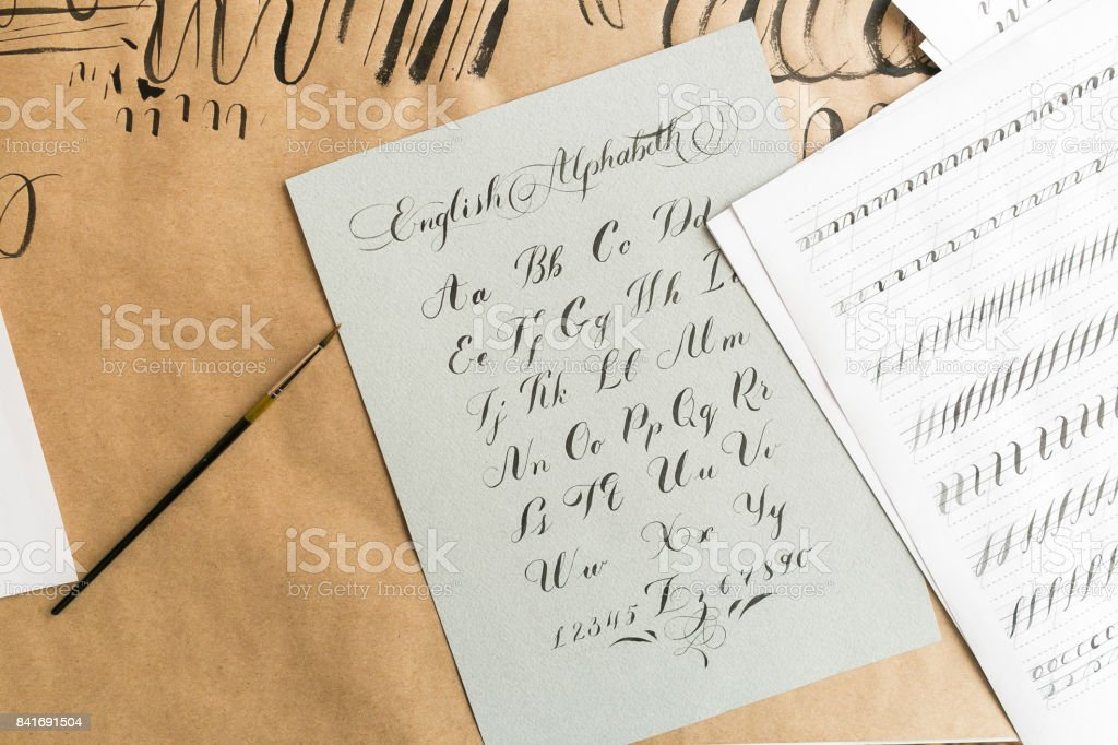visual art, education, handwriting concept. there is gorgeous lettering of english alphabeth and arabic numbers made in skillful manner on the textured grey paper stock photo