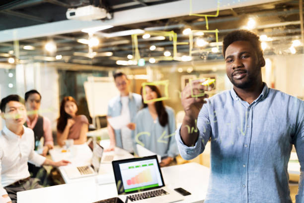 Visualizations are a key factor in overcoming our tasks Multi-ethnic group of young entrepreneurs having a business meeting in front of the transparent wipe board in the office project manager stock pictures, royalty-free photos & images