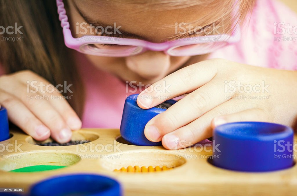 Visually disabled child playing with textured rolls closeup stock photo
